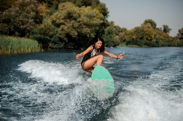 Donna attraente del brunette che pratica il surfing a bordo giù l'acqua blu