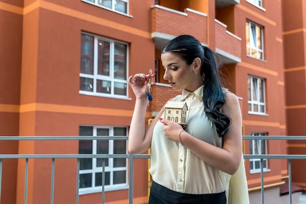 Attraente donna bruna con chiavi e modello di casa