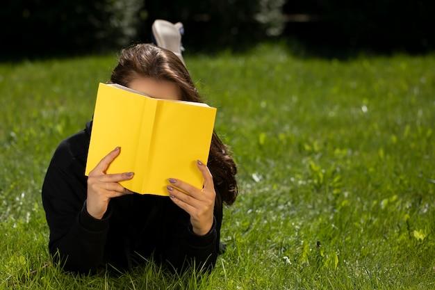 Attraente donna bruna con capelli lunghi vestita in felpa con cappuccio nera sdraiato sull'erba di prato verde leggendo il libro giallo in una bella giornata estiva