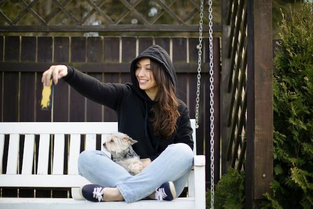 Attraente donna castana con capelli lunghi vestita in felpa con cappuccio nera che si siede sulla panchina bianca con cane yorkshire e fa selfie con il suo smartphone