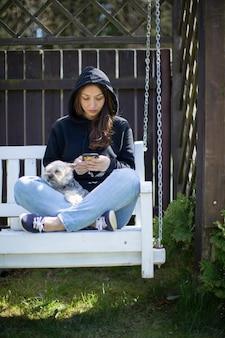 Attraente donna castana con capelli lunghi vestita in felpa con cappuccio nera che si siede sulla panchina bianca altalena con cane yorkshire e scrive messaggi sul suo smartphone