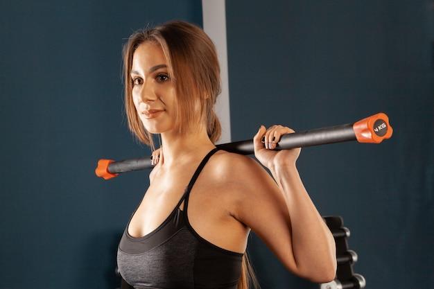 Donna attraente del brunette che risolve con il bodybar in ginnastica