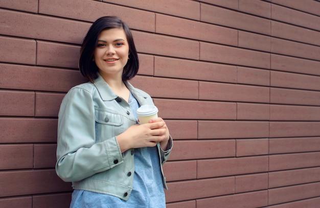 Attraente giovane donna bruna con tunnel nelle orecchie in una giacca di pelle beige con una tazza di caffè in piedi davanti al muro di mattoni.