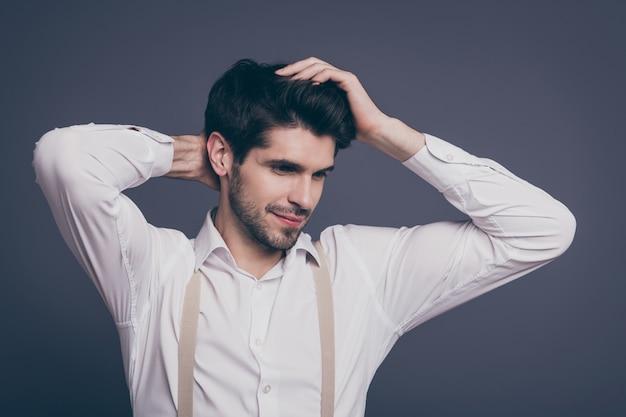Attraente uomo d'affari tocco macho acconciatura affascinante sorridente cerca spazio vuoto vestito abiti da cerimonia camicia bianca bretelle beige.