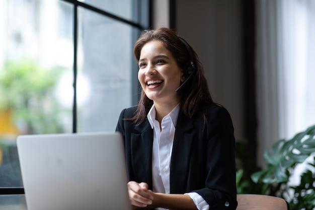 Attraente donna d'affari asiatica in giacca e cuffia sorride mentre lavora con il computer