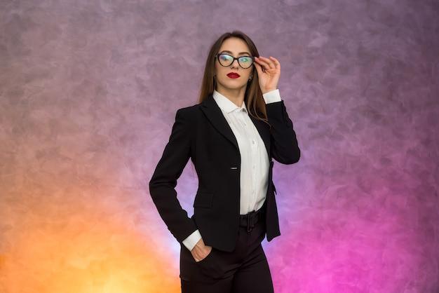 Attraente donna d'affari che gesturing ob sfondo astratto in occhiali originali