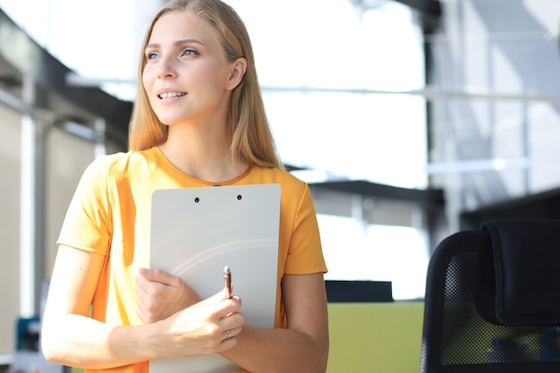 Attraente donna d'affari in abbigliamento casual intelligente che guarda lontano e sorride mentre si trova in ufficio.