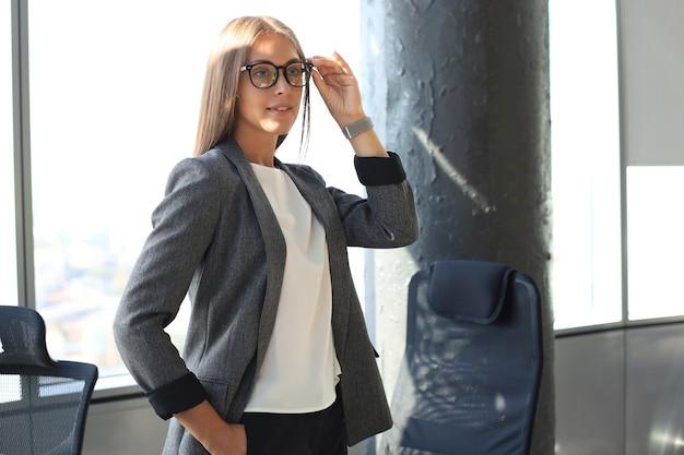 Attraente donna d'affari sorridente e tenendo gli occhiali mentre si trovava in ufficio.