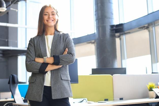 Donna attraente di affari che sorride mentre levandosi in piedi nell'ufficio.