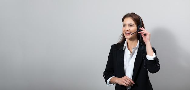Attraente donna d'affari in giacca e cuffia sorride mentre lavora in isolamento
