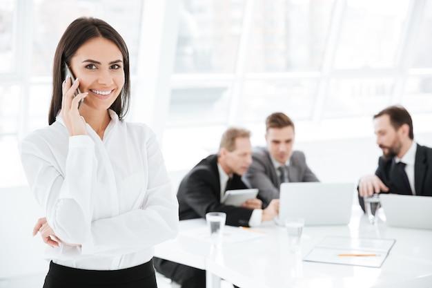 Attraente donna d'affari che parla al telefono con i colleghi in ufficio