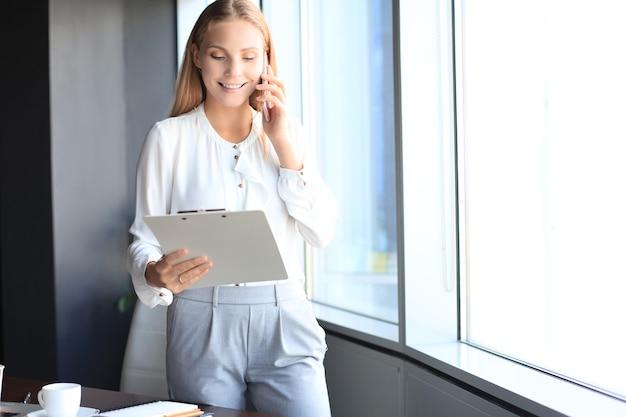 Attraente donna d'affari che parla con i colleghi al telefono cellulare mentre si trova vicino alla finestra in ufficio.