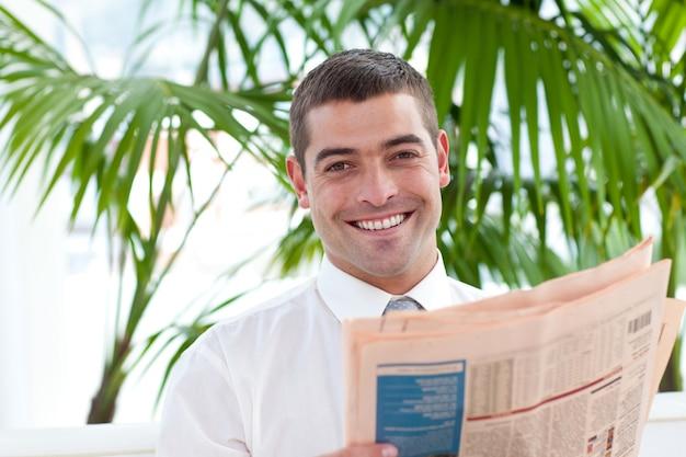 Uomo d'affari attraente che legge un giornale nel posto di lavoro