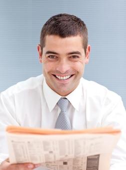 Uomo d'affari attraente che legge un giornale