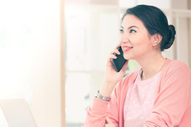 Tenuta attraente della donna di affari che si siede che lavora la sua piccola impresa da casa