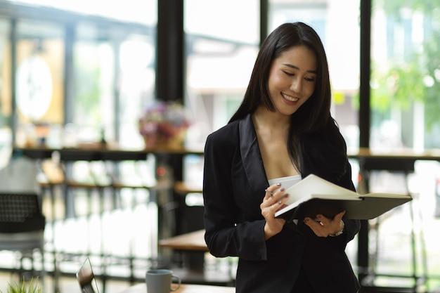 Attraente donna d'affari che legge guardando la sua agenda per il prossimo programma in ufficio