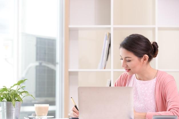 Attraente imprenditrice seduta lavorando sul portatile la sua piccola impresa da casa