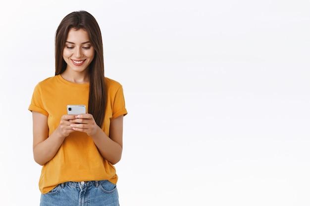 Attraente, spensierata emotiva giovane donna bruna in t-shirt gialla, con in mano lo smartphone sorridente eccitato, guardando lo schermo mobile, fare ordine, fare shopping venerdì nero, stare in piedi su sfondo bianco