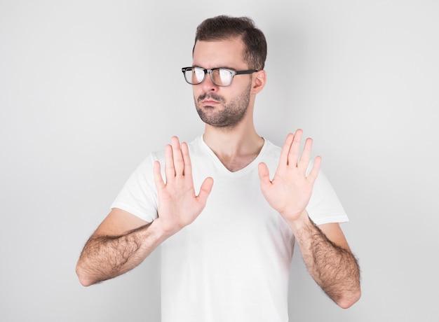 Attraente uomo caucasico con la barba con espressioni serie ti chiede di essere calmo e attento, segnale di stop
