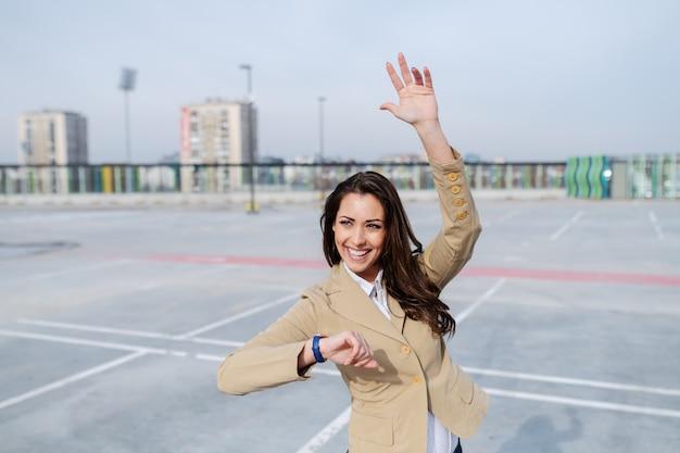 Il brunette caucasico attraente si è vestito in rivestimento beige che si leva in piedi sul parcheggio e che fluttua al tassista.