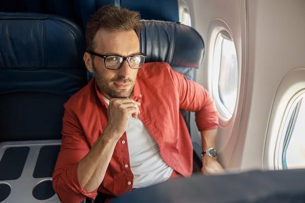 Attraente uomo d'affari caucasico in abbigliamento casual e occhiali dall'aspetto pensieroso, seduto sull'aereo vicino alla finestra. relax, viaggio, vacanza, concetto di trasporto