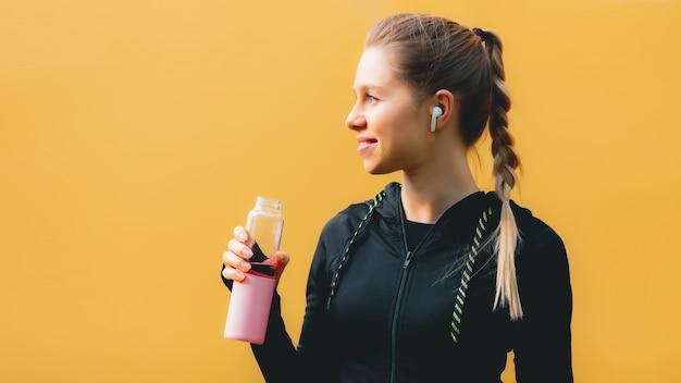 Attraente ragazza caucasica su sfondo giallo isolato con cuffie wireless in tuta sportiva fare allenamento, corsa e acqua potabile