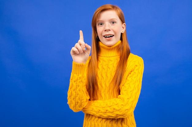 La ragazza dai capelli rossi caucasica attraente in un maglione giallo ha un'idea su uno studio blu