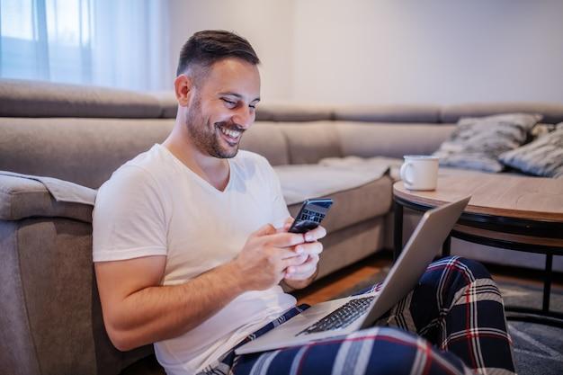 Uomo sorridente con la barba lunga caucasico attraente in pigiami che si siedono sul pavimento in salone con il computer portatile nel rivestimento e che scrivono messaggio sullo smart phone.