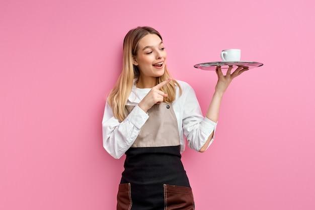 Attraente donna caucasica cameriera in grembiule tenendo il vassoio con il dito indice della tazza