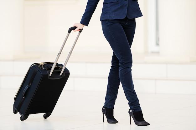 La donna caucasica attraente ha vestito i bagagli di trazione casuali astuti e andare all'aeroporto.