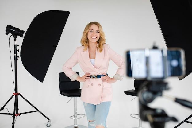 Attraente donna caucasica con capelli ondulati chiari in una camicia bianca, pantaloni blu le tiene le mani sulla vita e sorride in studio