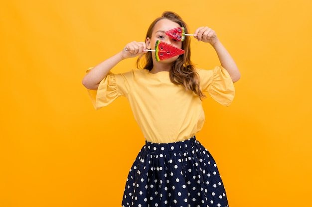 Ragazza caucasica attraente in una gonna e una maglietta con due lecca-lecca dell'anguria che posano sul giallo