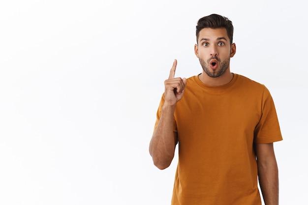 Attraente e affascinante collega hipster maschile suggerisce il suo metodo di soluzione, alza il dito indice in eureka, gesto della lampadina, piega le labbra dicendo il suo piano, introduce il proprio concetto durante la riunione d'ufficio