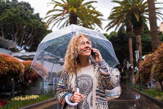 Attraente e allegra moda alla moda di mezza età giovane donna caucasica che cammina in città sotto la pioggia con un ombrello trasparente