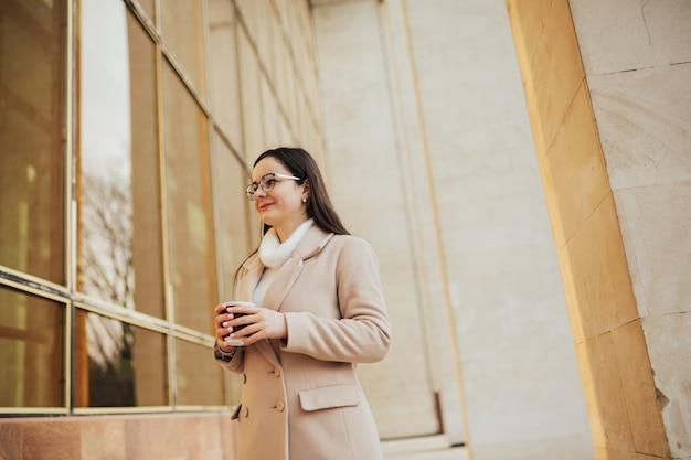 Attraente ragazza allegra in cappotto beige e occhiali da vista con caffè per andare a camminare all'aperto vicino all'edificio.