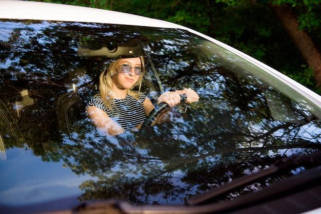 Attraente ragazza allegra conducente si siede al posto di guida di un'auto moderna.