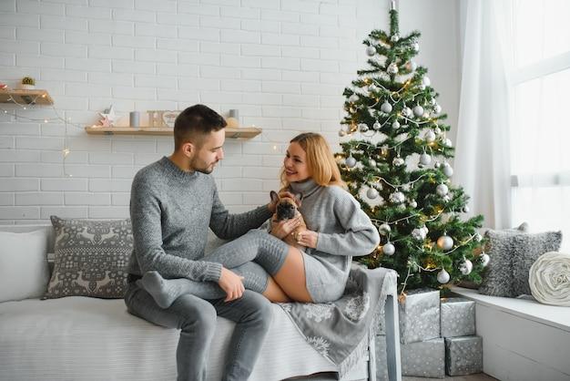 Attraente uomo allegro e donna seduta vicino all'albero di natale che abbraccia