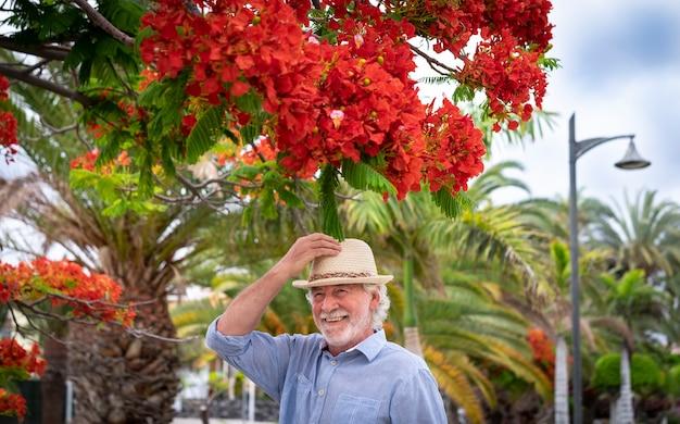 Attraente uomo anziano allegro con capelli bianchi e barba che sorride sotto una pianta fiorita nel parco che si tocca il cappello - concetto di pensionato rilassato e felice all'aperto