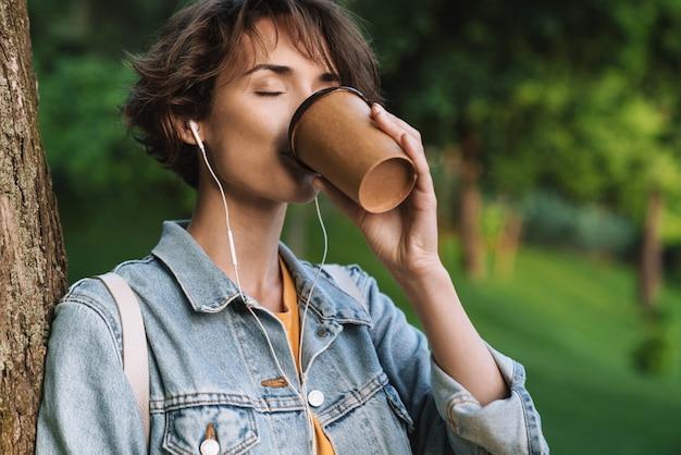 Attraente ragazza allegra che indossa un abbigliamento casual che trascorre del tempo all'aperto al parco, ascoltando musica con gli auricolari, tenendo in mano una tazza di caffè da asporto