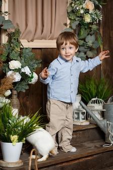Bambino attraente che gioca con il coniglietto di pasqua in un'erba verde. decorazione rustica. lo studio ha sparato su una priorità bassa di legno