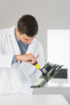 Ingegnere informatico attraente che ripara hardware con cacciavite