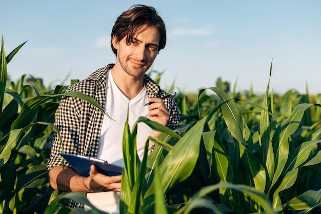 Uomo attraente e fiducioso che lavora in un campo di mais. l'agronomo guarda nella telecamera, tenendo appunti.