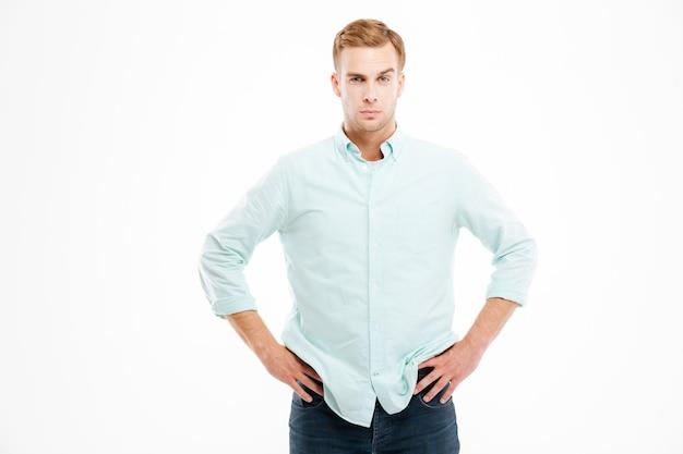Attraente giovane uomo d'affari fiducioso in piedi con le mani sui fianchi sul muro bianco white