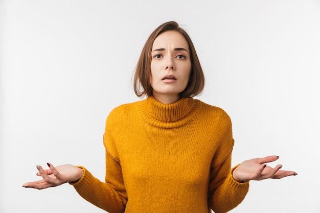Attraente giovane donna confusa in piedi isolata su muro bianco
