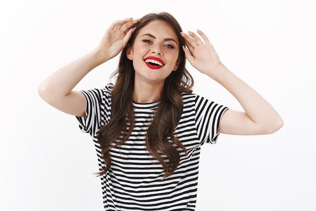 Attraente donna caucasica civettuola sembra seducente, sorride gioiosamente mostra il tatuaggio sul braccio, tocca la testa delicatamente metti via la ciocca di capelli, ridendo civettuola e sensualmente