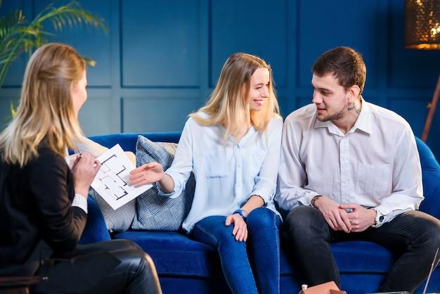 Coppia attraente durante l'incontro con agente immobiliare, interior designer, decoratore.