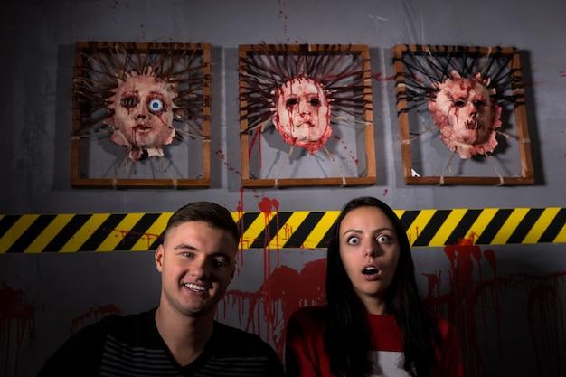 Coppia attraente di fronte a facce scuoiate per la spaventosa scena del crimine del terrore a tema halloween