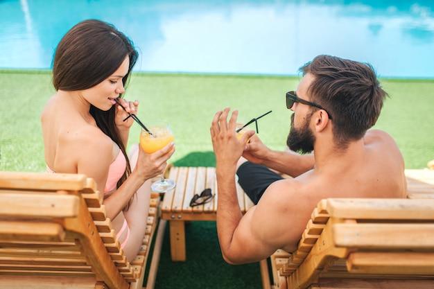 Coppia attraente è seduto su lettini e bere cocktail. la ragazza guarda in basso. tiene la paglia. guy indossa gli occhiali.
