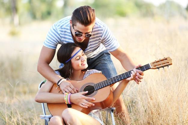 Coppia attraente che suona la chitarra, all'aperto