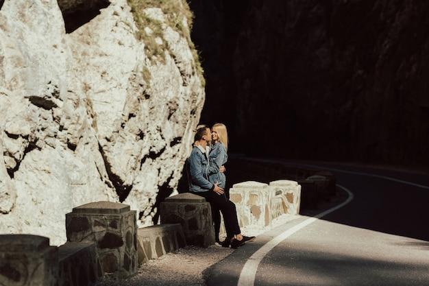 Coppia attraente in piedi sulla strada con rocce e pietre nel muro.